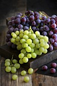 Red and green grapes on a wooden surface