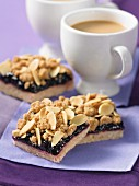 Linzer Schnitten (nutty shortcrust biscuits topped with jam) with crumbles and flaked almonds