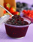 Raspberry and blackberry jam in a glass bowl and on a spoon
