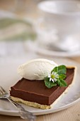 A slice of chocolate tart with yoghurt ice cream and mint