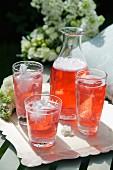 Erfrischender Aperol-Drink in Gläsern und Karaffe