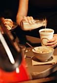 Kaffee im Pappbecher mit Milch aufgiessen, im Vordergund Würfelzucker in Schale