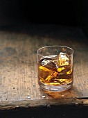 A glass of whiskey over ice on a wooden table