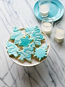 Christmas biscuits with blue icing and three glasses of milk