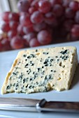 A slice of Roquefort and red grapes