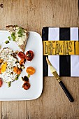 Fried eggs with fried tomatoes and bread-and-butter for breakfast