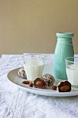Chocolate and almond truffle pralines with grated coconut and served with milk