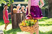 A girl carrying a basket of lemons to a lemonade stand