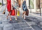 Three fashionably dressed young women with shopping bags in Cagliari (Sardinia, Italy)