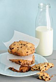 A stack of homemade hazelnut chocolate chip cookies with a bottle of milk