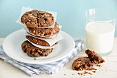 A stack of homemade hazelnut and chocolate cookies with a glass of milk