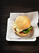 A hamburger with tomatoes, rocket and Munster cheese