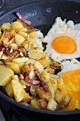 Fried potatoes with bacon and fried eggs