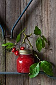 A jar of home-made cornelian cherry jam with a sprig against a wooden wall