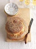 Sesame seed challa (Jewish bread) with a knife on a chopping board