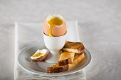 A soft-boiled egg in an egg cup with soldiers