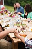 Um einen Tisch sitzende Menschen halten sich während des Tischgebets an den Händen
