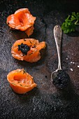 Black caviar on salmon rolls and on a spoon