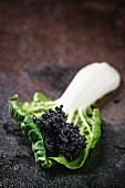 Black caviar on a chard leaf