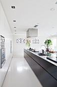 Lange, frei stehende Küchentheke mit schwarzen Unterschränken in Designerküche, abgehängte Decke mit Einbaustrahlern