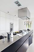 Lange, frei stehende Küchentheke mit dunklen Unterschränken in Designerküche
