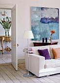 Sofa und Stehleuchte mit Ablage vor modernem Bild; Blick durch offene Tür auf antiken Konsolentisch in der Diele