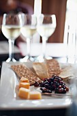 An appetizer platter featuring cheese, crisp breads and raisins with glasses of white wine in the background