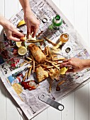Hands reaching for fish and chips on a piece of newspaper