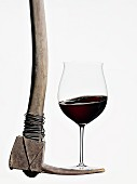 A glass of red wine balanced on a pick axe
