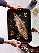 Hands holding a roast trout in a roasting tin
