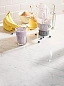 Heidelbeer-Bananenshake im Mixkrug und in einem Glas mit Zucker und Honig
