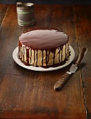 Banana cake with caramel buttercream and chocolate glaze on a wooden table