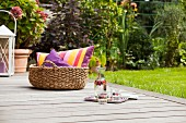 Carafe, glasses and basket of cushions on wooden deck