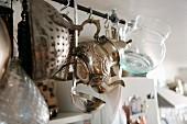 Von Decke abgehängte Stange mit verzierter Metallkanne und Glaskrug zwischen Küchenutensilien