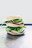 A sesame seed bagel topped with ham, Asiago cheese and lambs lettuce