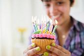 Hände mit gelb lackierten Fingernägeln halten einen Geburtstags-Cupcake