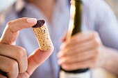A man holding a red wine cork