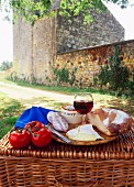 A picnic of bread, cheese, tomatoes and red wine on a hamper in the Dordogne, France