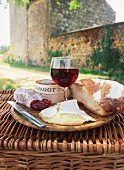 A picnic with bread, red wine, cheese and sausage on top of a wicker basket in the Dordogne, France, Europe