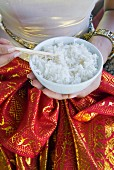 Hands holding a bowl of rice, Thailand, South-East Asia
