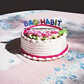A birthday cake with candles spelling the phrase 'Bad habit'
