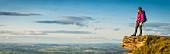 Junger Wanderer auf Felsvorsprung mit Panoramaausblick