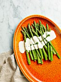 Asparagus with a white sauce on a plate