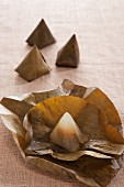 Steamed rice flour pyramids wrapped in banana leaves (dessert from Thailand)