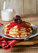 A stack of pancakes topped with blackberry sauce with a bottle of milk in the background