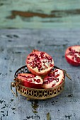 Pomegranate halves in a metal dishes and next to it