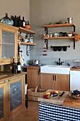 Rustikale Küche mit hellen Holzmöbeln, Spülbecken und Wandregalen