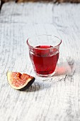 A glass of red wine and a fig