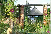 A view of a thatched roof house with a wild garden, Quilitz in Lieper Winkel, Usedom, Mecklenburg-Vorpommern