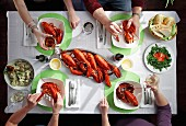 Four people eating a lobster dinner